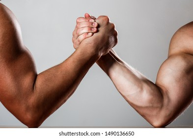 Hand wrestling, compete. Hands or arms of man. Muscular hand. Clasped arm wrestling. Two men arm wrestling. Rivalry, closeup of male arm wrestling. Muscular men measuring forces, arms.