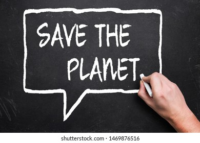 "hand writes ""save the planet"" with chalk on a blackboard"