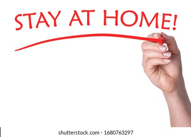 Hand writes word stay at home with red marker on transparent white background.