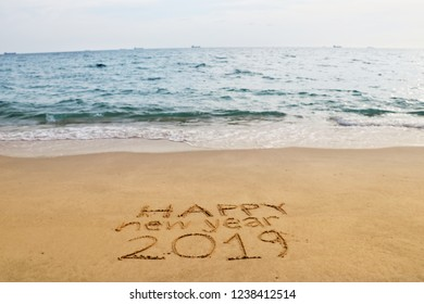 hand writing 2019 and happy newyear message in the sand beach