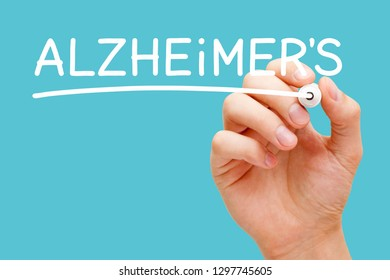 Hand writing Alzheimers disease with white marker on transparent wipe board isolated on blue background.