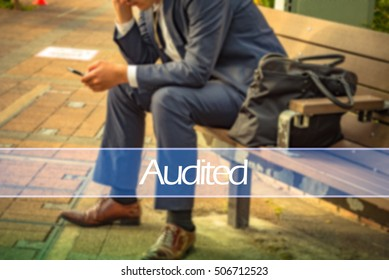 Hand writing audited with the abstract background. The word audited  represent the action in business as concept in stock photo.