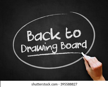 A hand writing 'Back to Drawing Board' on chalkboard.