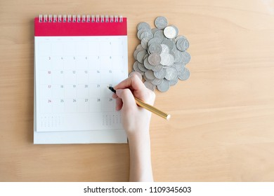 Hand writing in calendar plan and coins concept