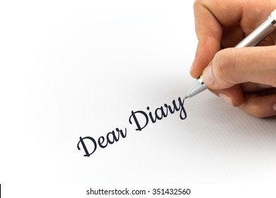 """Hand writing """"Dear Diary"""" on white sheet of paper."""