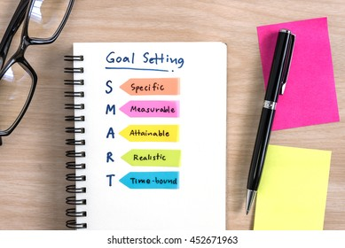 Hand writing definition for smart goal setting on notebook with pen, eye glasses and colorful sticky note on desk