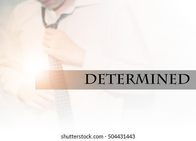 Hand writing DETERMINED with the abstract bokeh on background. This word represent the business as concept in stock photo.