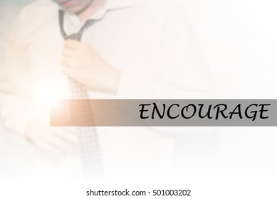 Hand writing ENCOURAGE with the young business man on background. Business concept. Stock Photo.