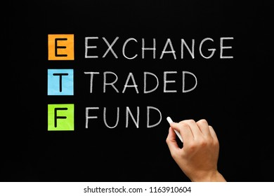 Hand writing ETF - Exchange Traded Fund with white chalk on blackboard.