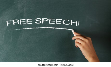 Hand writing Free Speech! on a blackboard
