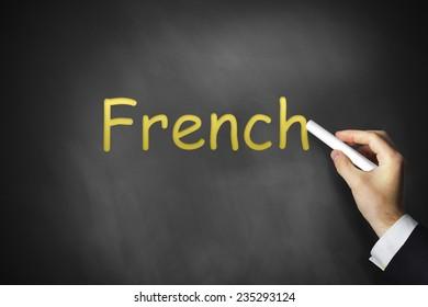 hand writing french on black chalkboard