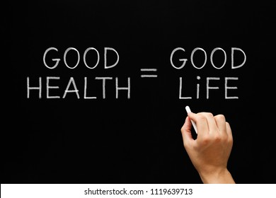 Hand writing Good Health Equals Good Life with white chalk on blackboard.