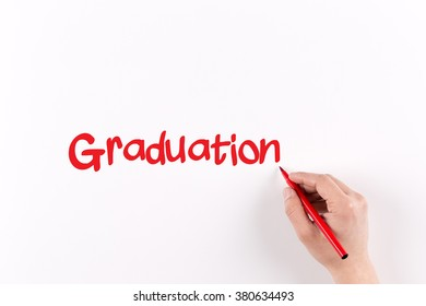 Hand writing GRADUATION on white paper, View from above