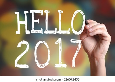 Hand writing Hello 2017 with marker on transparent wipe board with bokeh lights background.