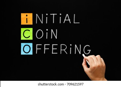 Hand writing ICO - Initial Coin Offering with white chalk on blackboard.