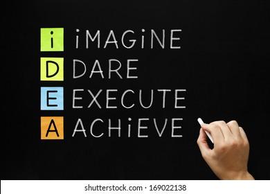 Hand writing IDEA - Imagine Dare Execute Achieve with white chalk on blackboard.