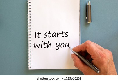 Hand writing 'it starts with you' on white note, isolated on blue background.