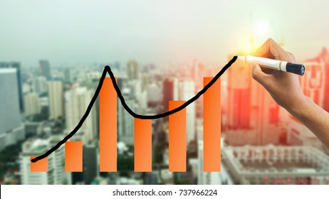hand writing line graph and bar chart graph  graphic with blur city town background. business continue growth concept, business life cycle concept. business forecast concept