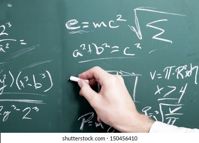 a hand writing math equations upon a chalkboard