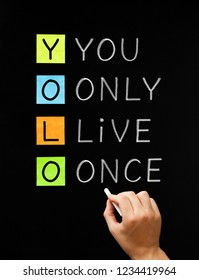 Hand writing the motto acronym YOLO - You Only Live Once with white chalk on blackboard.