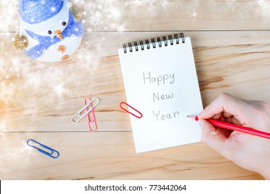 Hand is writing New Year Memo Note and snowman on wooden table.