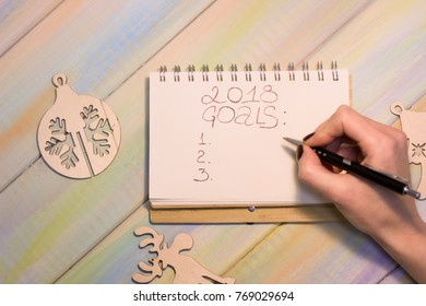 A hand writing in a notebook with 2018 goals inscription on a light colorful wooden table, wooden flat Christmas-tree toys. Top view