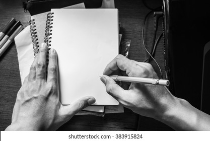 Hand writing notebook on working table, with copy space, black and white, monochrome