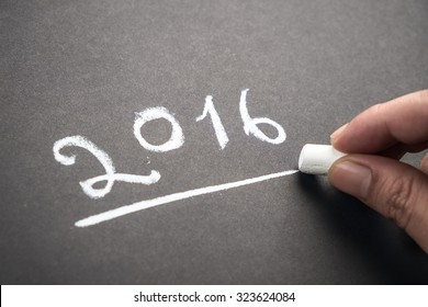 Hand writing numbers of year 2016 on chalkboard
