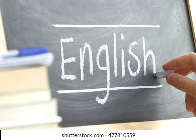 "Hand writing on a blackboard in an language class with the word ""English"" wrote in. Some books and school materials."
