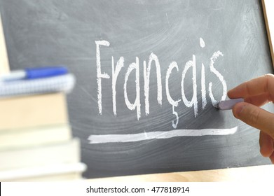 "Hand writing on a blackboard in a language class with the word ""French"" written on it. Some books and school materials."