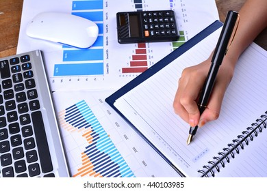 Hand writing on blank notebook with graph, chart, keyboard, mouse and calculator on wooden table
