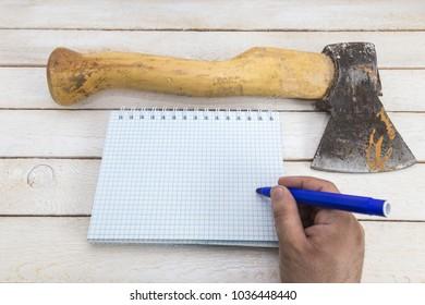 Hand writing on blank notepad near the Ax. killer's note