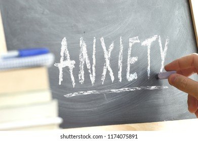 Hand writing on a chalk board the word Anxiety in a mental health class. Psychology disorder concept.