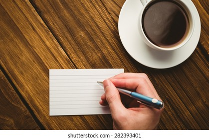 Hand writing on the flashcard on a desk