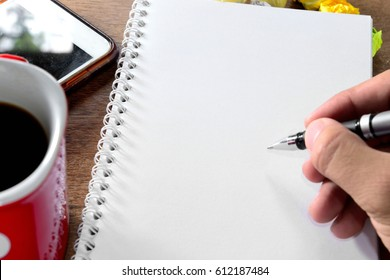 Hand writing on notebook with coffee cup beside smart phone and crumpled papers on wood table , hands with pen writing on notebook , Business still life concept