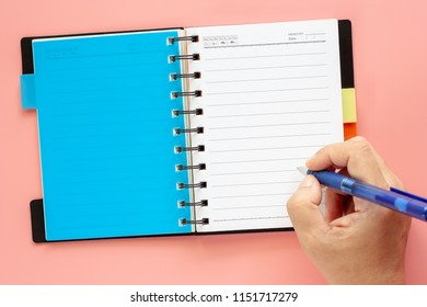 Hand writing on an opened blank notebook with pen on pink background for education and office supplies. Back to school concept