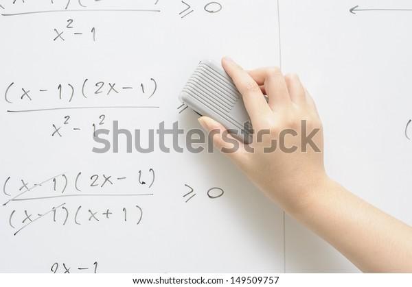 a hand writing on whiteboard