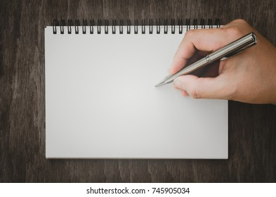 Hand writing with pen on empty notepad on wooden table background