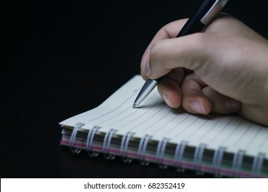 Hand writing with pen on notebook.