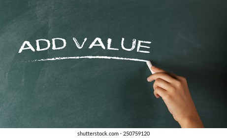 Hand writing the phrase Add Value on a blackboard