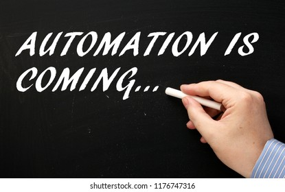 Hand writing the phrase Automation is Coming on a blackboard as a reminder for business and workers to prepare and plan ahead