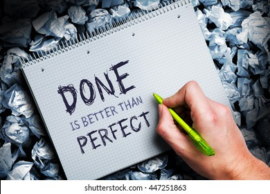 """hand writing phrase """"Done is better than perfect"""" on a block, surrounded by many crumpled paper balls"""