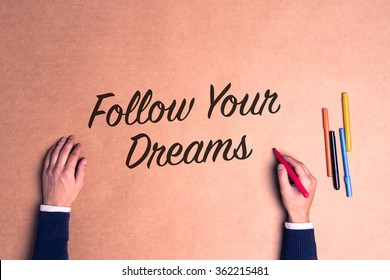 Hand writing a phrase Follow Your Dreams on paper