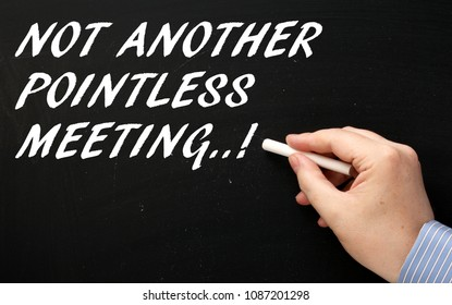Hand writing the phrase Not Another Pointless Meeting on a blackboard as a reminder not to waste time in business
