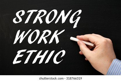 Hand writing the phrase Strong Work Ethic in white text on a blackboard as a reminder of the characteristics required for success