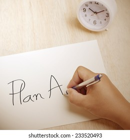 Hand writing Plan A on paper sheet