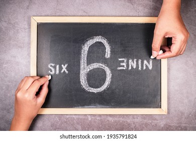Hand writing from the point of view of 6 and 9 number on chalkboard in opposite direction, argument in different perspectives concept