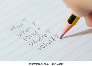 Hand writing questions on paper for brainstorming, uncertainty or decision making concept
