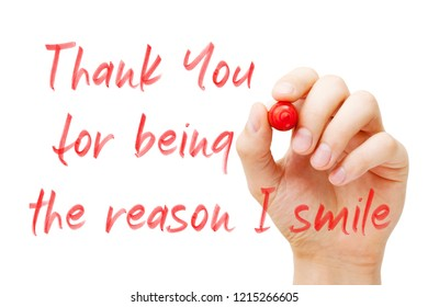 Hand writing quote Thank You For Being The Reason I Smile with red marker on transparent wipe board isolated on white.