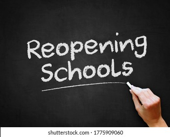 A hand writing 'Reopening Schools' on chalk board for schools reopening plans after Covid-19 (Coronavirus) pandemic lockdown. - Shutterstock ID 1775909060